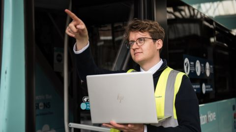 Tim Griffen Engineering Graduate using laptop to inspect bus (4).jpg